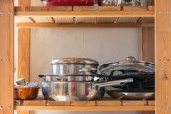 罐和平底锅在木厨房架子倒空烹调Equipm的空间 免版税库存照片