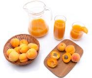 水罐和杯与整个和被切的成熟apri的杏子汁 免版税库存图片
