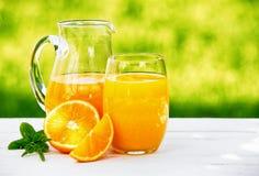 水罐和杯新鲜的橙汁 库存图片