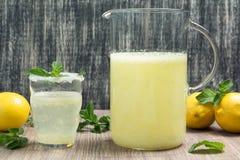 水罐和杯柠檬水whith在木桌上铸造 免版税图库摄影