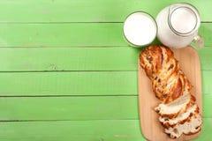水罐和杯牛奶用一个面包在绿色木背景的与您的文本的拷贝空间 顶视图 免版税库存图片