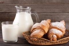 水罐和杯牛奶用在木背景的新月形面包 库存照片