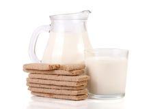 水罐和杯牛奶用在白色背景隔绝的五谷薄脆饼干 免版税库存照片