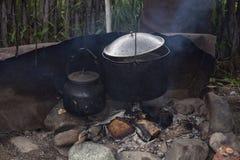 罐和通入蒸汽的水壶在壁炉边 免版税库存图片
