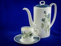 罐和配比的杯子反对品蓝背景 免版税库存照片