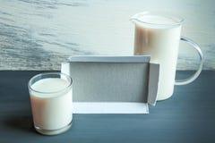 水罐和玻璃杯子用杏仁在木桌上挤奶 乳糖释放不宽容 库存图片