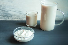 水罐和玻璃杯子用牛奶和酸性稀奶油在木桌上 乳糖释放不宽容 图库摄影