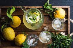 水罐和玻璃用自创柠檬水,冰块在木盘子,顶视图 库存照片