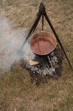 罐在三脚架的炖煮的食物 库存照片