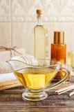 水罐在木桌上的金黄液体皂 免版税图库摄影