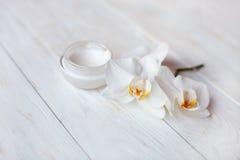 罐在白色木桌上的润湿的面霜 免版税图库摄影