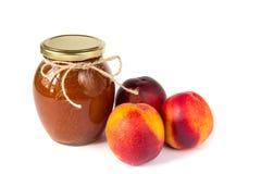 罐在白色背景的果酱用成熟开胃桃子 免版税库存图片
