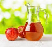 水罐在自然背景的苹果汁 图库摄影