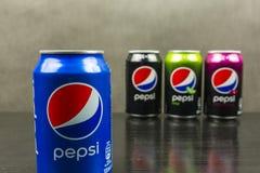 罐头用原始的百事可乐是在一种传统蓝色颜色 在背景中,罐头的其他颜色p的其他味道的 库存照片
