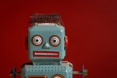 罐子反对红色背景的玩具机器人 库存照片