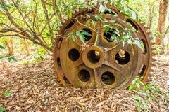 罐子挖泥机大生锈的齿轮在离开的锡矿 干燥叶子在地面,热带森林背景上落 免版税库存图片