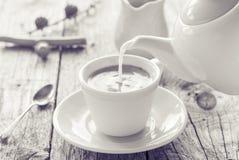 从水罐杯子无奶咖啡的倾吐的牛奶 免版税库存照片