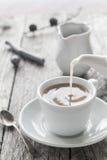 从水罐杯子无奶咖啡的倾吐的牛奶 图库摄影