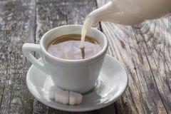 从水罐杯子无奶咖啡的倾吐的牛奶 库存图片