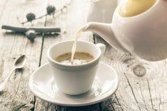 从水罐杯子无奶咖啡的倾吐的牛奶 免版税库存图片