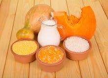 水罐用牛奶、谷物和南瓜在背景光木头 免版税库存图片
