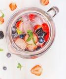 水罐用莓果浇灌和在白色木背景,顶视图,关闭的冰块  免版税图库摄影