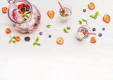 水罐用莓果浇灌,冰块、玻璃和成份在白色木背景,顶视图 免版税图库摄影