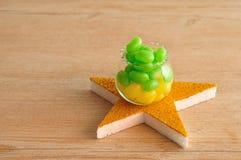罐用黄色和绿色豆形软糖填装了在一个金黄星顶部 免版税库存照片