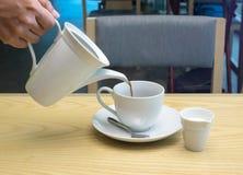 从水罐的倾吐的咖啡到在木桌上的杯子 免版税库存图片