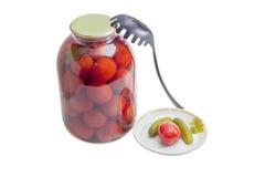 罐装蕃茄和黄瓜在茶碟和在玻璃瓶子 免版税库存图片