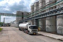 罐车,卡车交付危险化学制品在石油化工厂 免版税库存照片