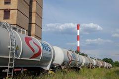 罐车从Nafta Industria通过在一个工厂烟囱附近的Srbije训练在塞尔维亚首都一个工业区  免版税库存图片