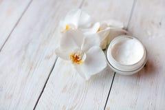 罐面霜和美丽的白色兰花在白色木桌上开花 免版税图库摄影