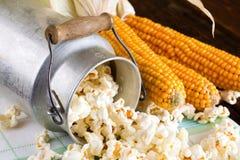 从罐头和少量棒子的溢出的玉米花 免版税库存图片