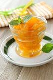 从罐头的橘子在玻璃和薄菏叶子 免版税库存图片