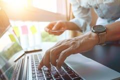 网上付款,人` s递拿着caredit卡片和使用膝上型计算机 库存图片