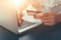 网上付款,人` s递拿着caredit卡片和使用膝上型计算机 免版税图库摄影