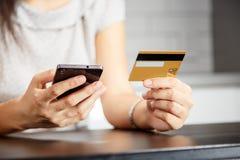 网上付款,妇女` s递拿着信用卡和使用巧妙的电话网上购物的 库存照片