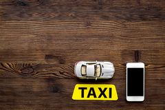 网上命令有流动app和汽车式样木桌背景顶视图大模型的一辆出租汽车 免版税图库摄影