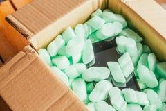 网上商店,在一个纸板箱的电话小包在绿色聚苯乙烯泡沫塑料 免版税图库摄影
