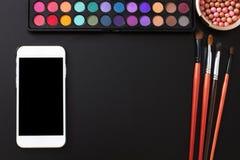 网上商店 化妆产品,在黑背景组成辅助部件 空白移动电话屏幕 顶视图和拷贝空间 免版税库存图片