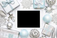 网上圣诞节购物 节礼日销售背景 被包裹的圣诞节礼物、装饰品和黑屏数字式片剂 库存照片