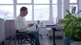 网上学会,自由职业者人残疾在轮椅戴着眼镜使用坐一个的手机在与计算机的桌 股票视频