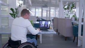网上教育,在轮椅致残的成熟学习者在笔记本写笔记,当观看训练开会在a时 影视素材