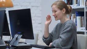 网上由红头发人妇女的网录影闲谈在工作,挥动的手 免版税图库摄影