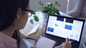 网上讲座,女生画在坐在桌上的笔记本和用途计算机膝上型计算机的折线图 股票录像