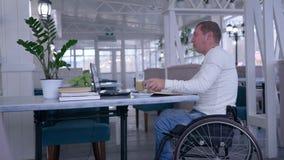 网上课程,学生轮椅的被致残的人用坐一份的膝上型计算机和饮用的咖啡在与书的桌在a 影视素材