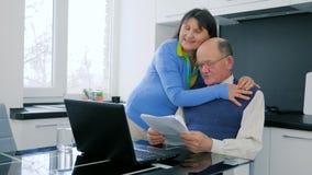 网上购物愉快的年长夫妇付款在网上与享受在事务的成功和拥抱在桌上的膝上型计算机 股票录像