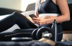 网上锻炼路线、个人教练员服务或者健身应用程序在电话 使用智能手机的适合妇女,当在家时解决 免版税库存图片