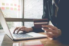 网上付款,女商人` s递拿着信用卡 库存照片